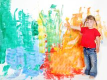 Young happy child girl painting white wall Stock Photo