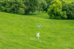Young happy child girl playing with bright kite in park Stock Photo