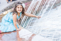 Young happy child girl playing with water fountain, outdoor port Royalty Free Stock Images