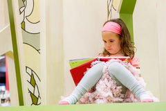 Young happy child girl reading a book Royalty Free Stock Images
