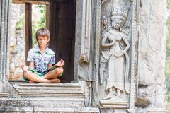 Young happy child girl tourist meditating in angkor wat, cambodi Royalty Free Stock Photography
