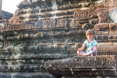 Young happy child girl tourist meditating in angkor wat, cambodi Stock Photo