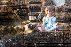 Young happy child girl tourist meditating in angkor wat, cambodi Stock Images