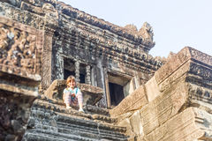 Young happy child girl tourist meditating in angkor wat, cambodi Royalty Free Stock Photo