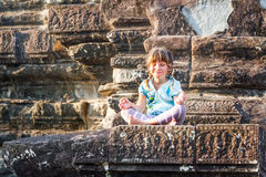 Young happy child girl tourist meditating in angkor wat, cambodi Royalty Free Stock Image