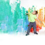 Young happy child painting white wall Royalty Free Stock Photography