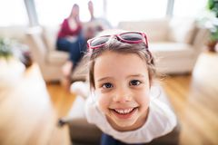 Young happy child with parents in the background packing for holidays. Young happy child with parents in the background packing for holidays at home Royalty Free Stock Images