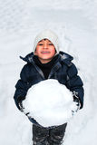 Young happy child playing with a big snow ball Royalty Free Stock Photo