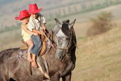 Young happy children riding horse Royalty Free Stock Photo