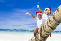 Young happy children in santa hats on tropical beach backgro Royalty Free Stock Photo