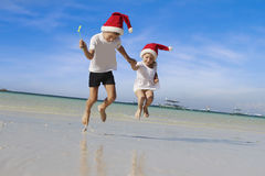 Young happy children in santa hats on tropical beach backgro Royalty Free Stock Images