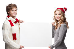 Young happy christmas couple holding big sign. Young casual caucasian couple in red scarf and hat holding big sign with nice smiles Stock Photo