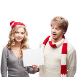Young happy christmas couple holding sign Royalty Free Stock Photography