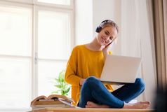 A young female student sitting at the table, using headphones when studying. royalty free stock photography