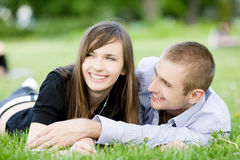 Young happy couple. Laying on grass Stock Photos