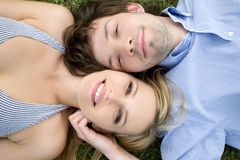 Young happy couple. Laying on grass Royalty Free Stock Photos