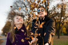 Young happy couple with autumn leaves Stock Images