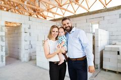 Young couple with a baby at the construction site. Young happy couple with a baby boy at the construction site Stock Photography