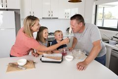 Young happy couple baking together with little son and young beautiful daughter at home kitchen having fun playing with cream. In family lifestyle and nutrition royalty free stock image