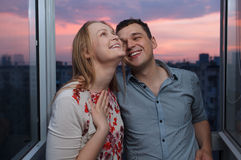 Young happy couple on the balcony. Playful young couple enjoying their new own apartment Royalty Free Stock Photos