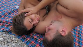 Happy Young Couple Lying On The Beach In Swimsuits Hugging Kissing. Young happy couple in bathing suits lying on a blanket pebble beach. Caress, Pat the face stock video footage