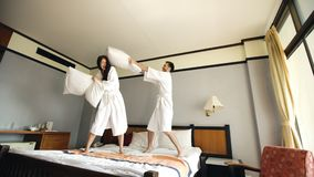 Young happy couple in bathrobe fight pillows and have fun on bed in hotel during their honeymoon vacation. Young happy couple in bathrobe fight pillows on bed in Royalty Free Stock Photography