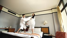 Young happy couple in bathrobe fight pillows and have fun on bed in hotel during their honeymoon vacation. Young happy couple in bathrobe fight pillows on bed in Royalty Free Stock Image