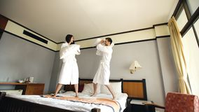Young happy couple in bathrobe fight pillows and have fun on bed in hotel during their honeymoon vacation. Young happy couple in bathrobe fight pillows on bed in Stock Photos