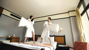 Young happy couple in bathrobe fight pillows and have fun on bed in hotel during their honeymoon vacation. Young happy couple in bathrobe fight pillows on bed in Royalty Free Stock Photos