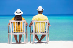 Young happy couple at beach chair looking at Royalty Free Stock Photography