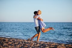 Young happy couple on beach at summer vacation. Young happy couple on beach near the sea at summer vacation royalty free stock photography