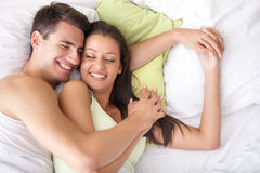 Young happy couple in bed Stock Photography