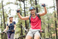 Young happy couple on bikes looking at camera Royalty Free Stock Image