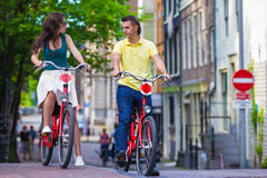 Young happy couple on bikes in old streets in Royalty Free Stock Photos