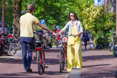 Young happy couple on bikes in old streets in Royalty Free Stock Images