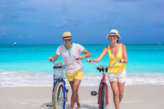 Young happy couple with bikes on white sandy beach Stock Photo