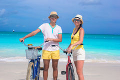 Young happy couple with bikes on white sandy beach Royalty Free Stock Photography