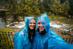 Young happy couple in blue raincoat stand in rain by river stock photography