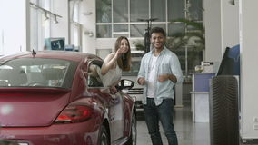 Young happy couple bought a car in car showroom. Happy swarthy guy looks on girl in car and smiling. Pretty girl appears from car`s window and demonstrate the stock video footage