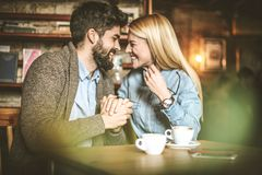 Happy and cheerfully couple at cafe. Young happy couple at cafe having conversation and looking each other Royalty Free Stock Photos