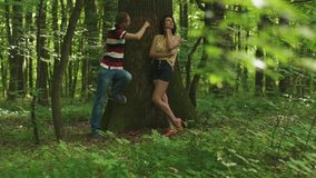 Young happy couple carving a heart with their initials on a tree. Green spring forest background.  stock footage