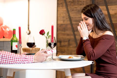 Young happy couple celebrating engagement proposal with a dinner at home and a gift Royalty Free Stock Photos