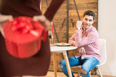 Young happy couple celebrating Valentine`s day with a dinner at. Young happy couple celebrating  Valentine`s day with gifts and a dinner at home Royalty Free Stock Photos