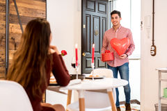 Young happy couple celebrating Valentine`s day with a dinner at. Young happy couple celebrating  Valentine`s day with gifts and a dinner at home Royalty Free Stock Photography