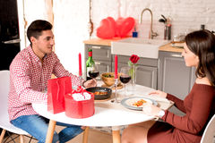 Young happy couple celebrating Valentine`s day with a dinner at home. Young happy couple celebrating  Valentine`s day with a dinner at home Royalty Free Stock Images
