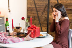 Young happy couple celebrating Valentine`s day with a gift. At home Royalty Free Stock Photos