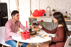 Young happy couple celebrating Valentine`s day with a gift. At home Stock Image