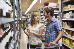 Young happy couple chooses wine in supermarket Royalty Free Stock Images