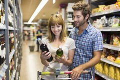 Young happy couple chooses wine in supermarket Stock Photos