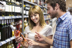 Young happy couple chooses wine in supermarket Royalty Free Stock Photo